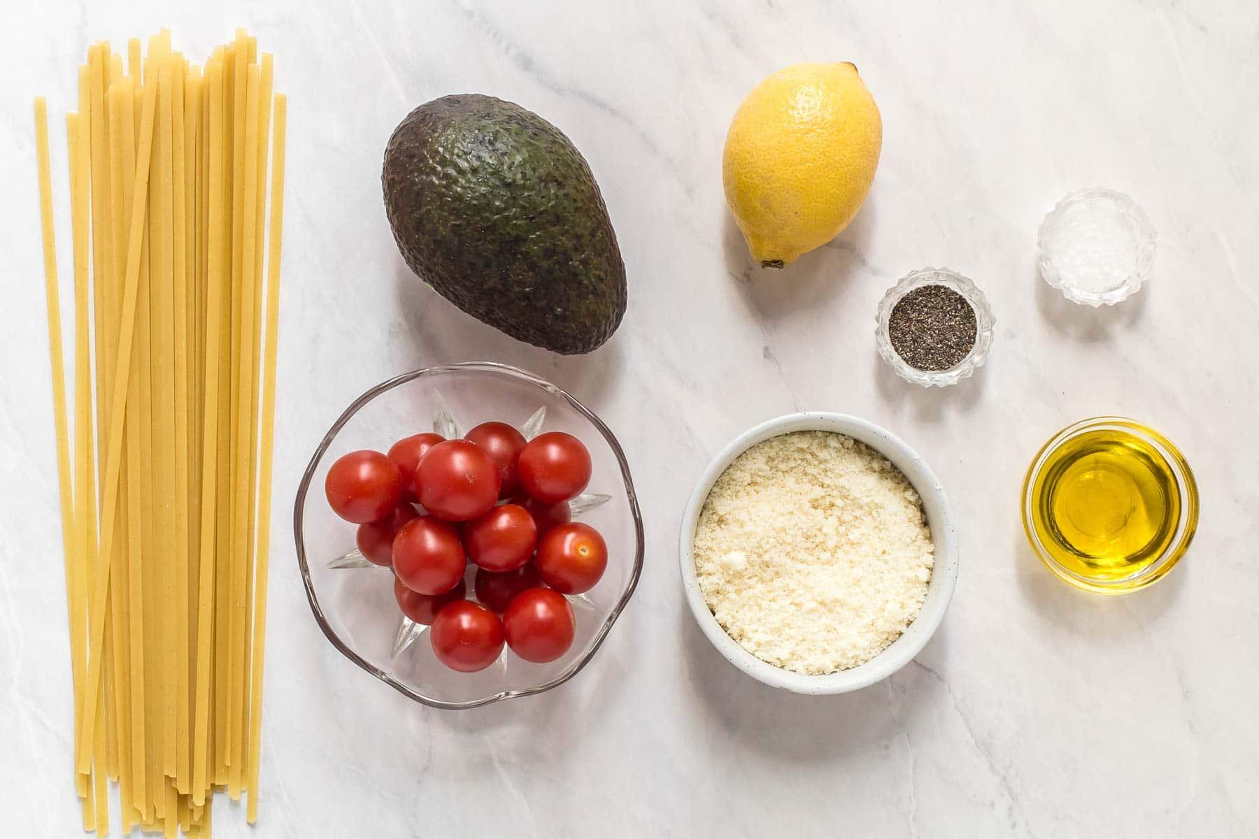 Ingredients for avocado pasta sauce on white table.