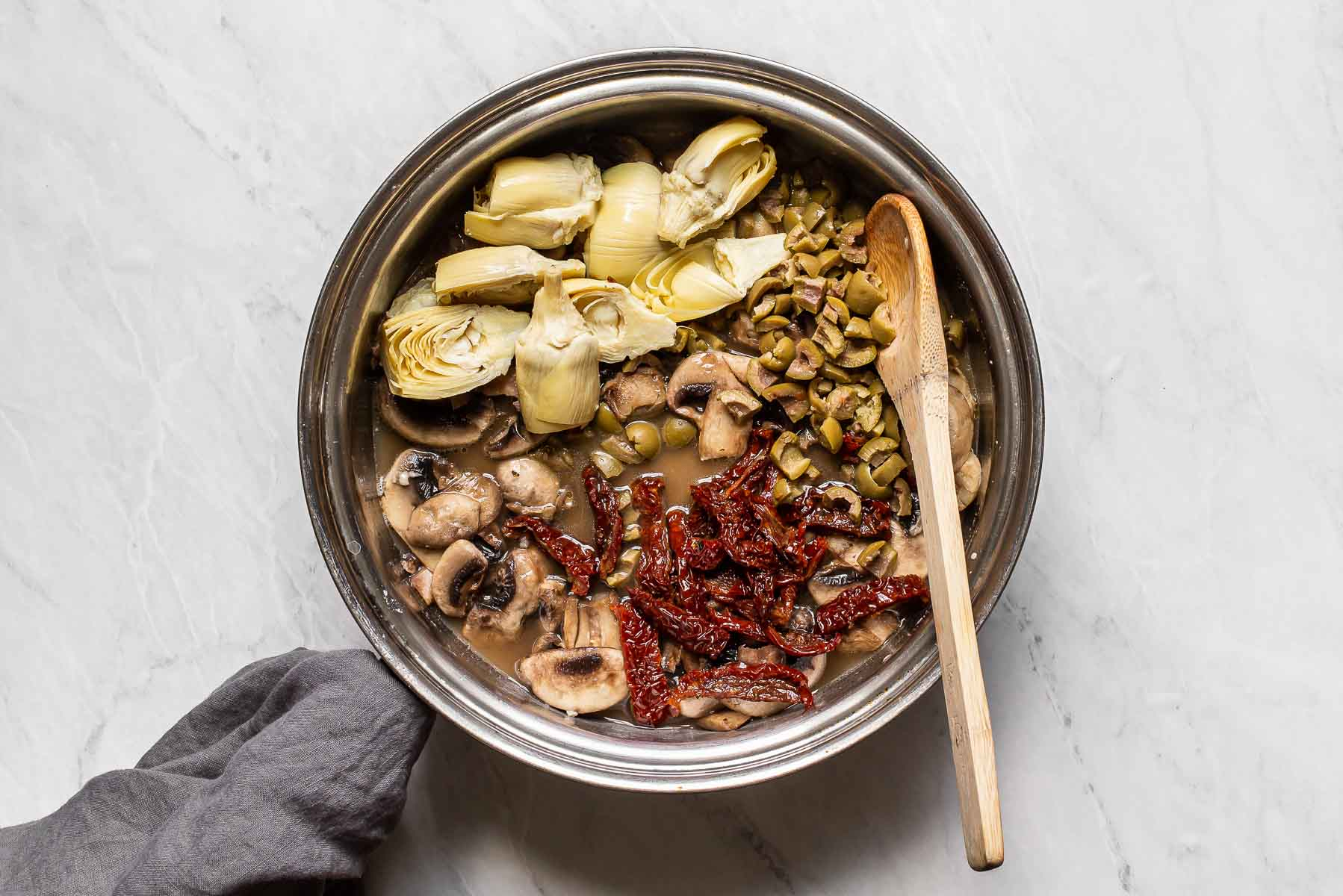 Artichokes, olive, mushrooms, and sun-dried tomatoes in skillet.