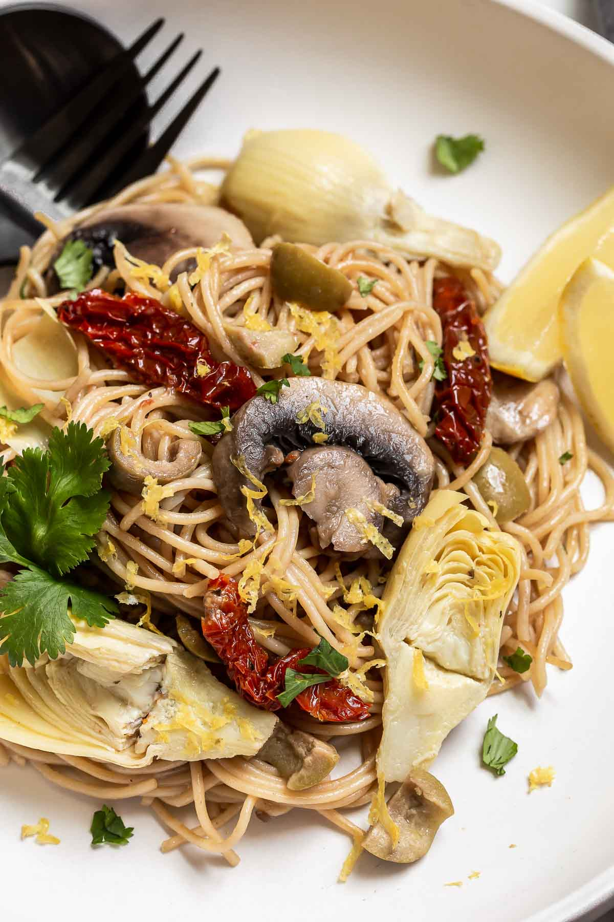 Pasta with sundried tomatoes and mushrooms on plate.