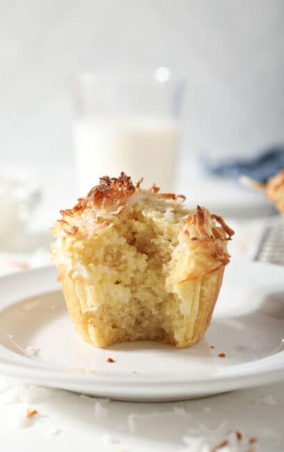 Coconut muffin on plate with bite missing.