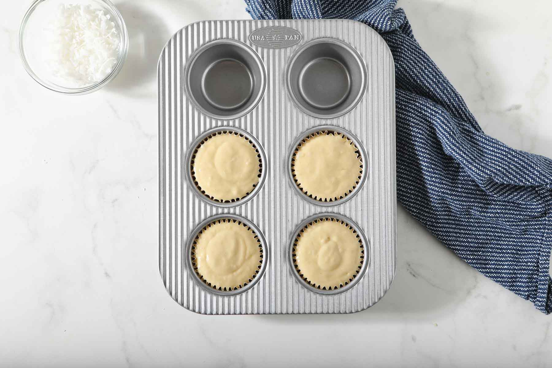 Raw coconut muffin batter in pan.