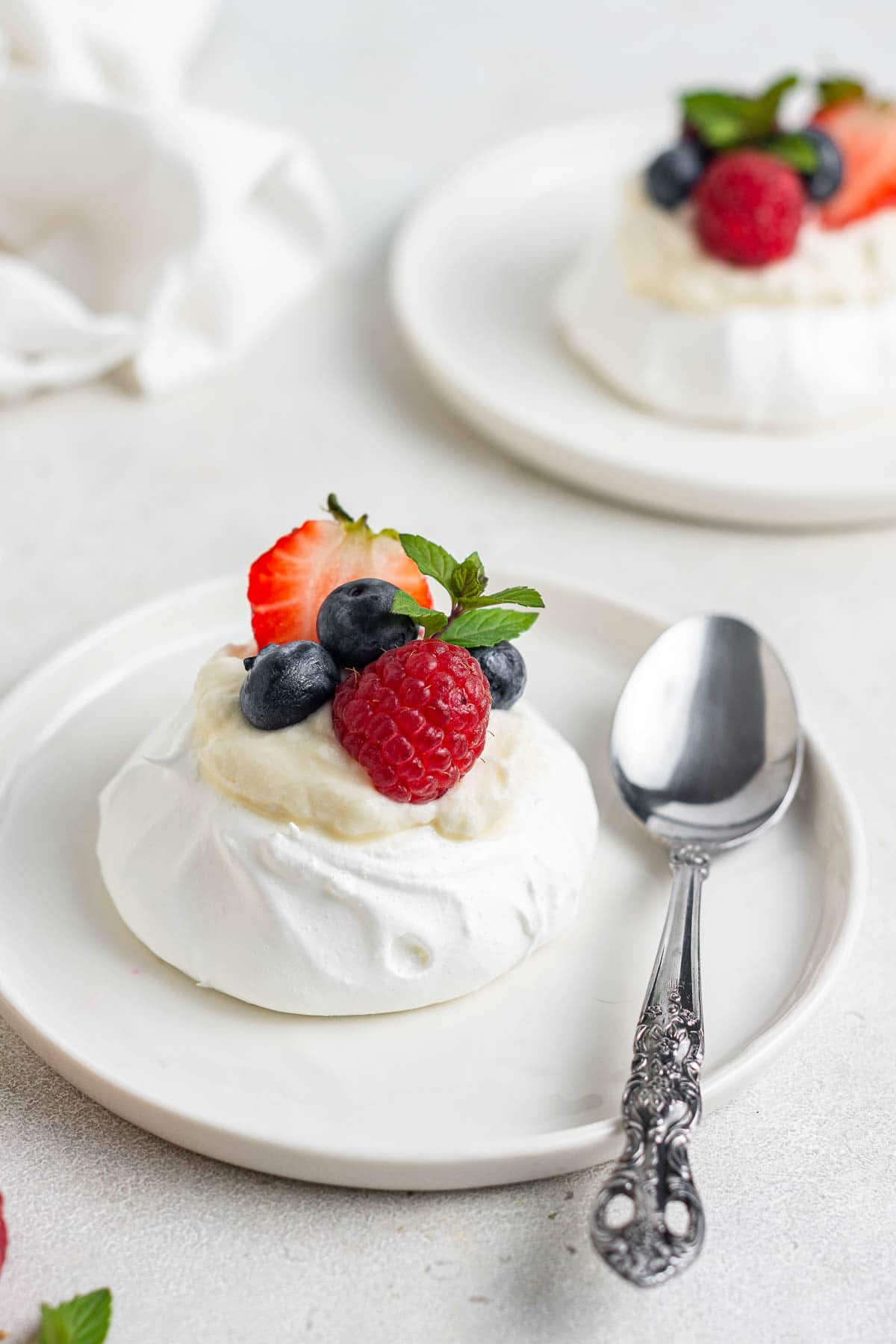 Mini pavlova on white plate with fresh berries on top.