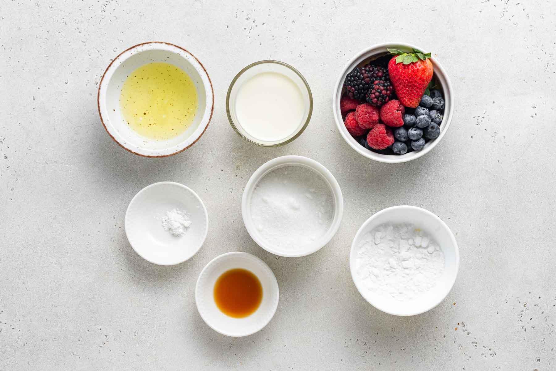 Ingredients for mini pavlova on white table.