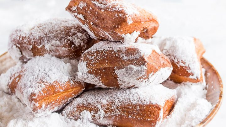 Homemade beignets from scratch in bowl with powdered sugar.