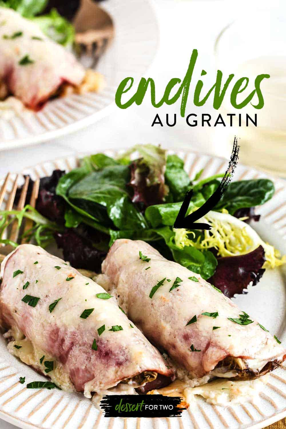 Two endives au gratin on white plate with salad mix.