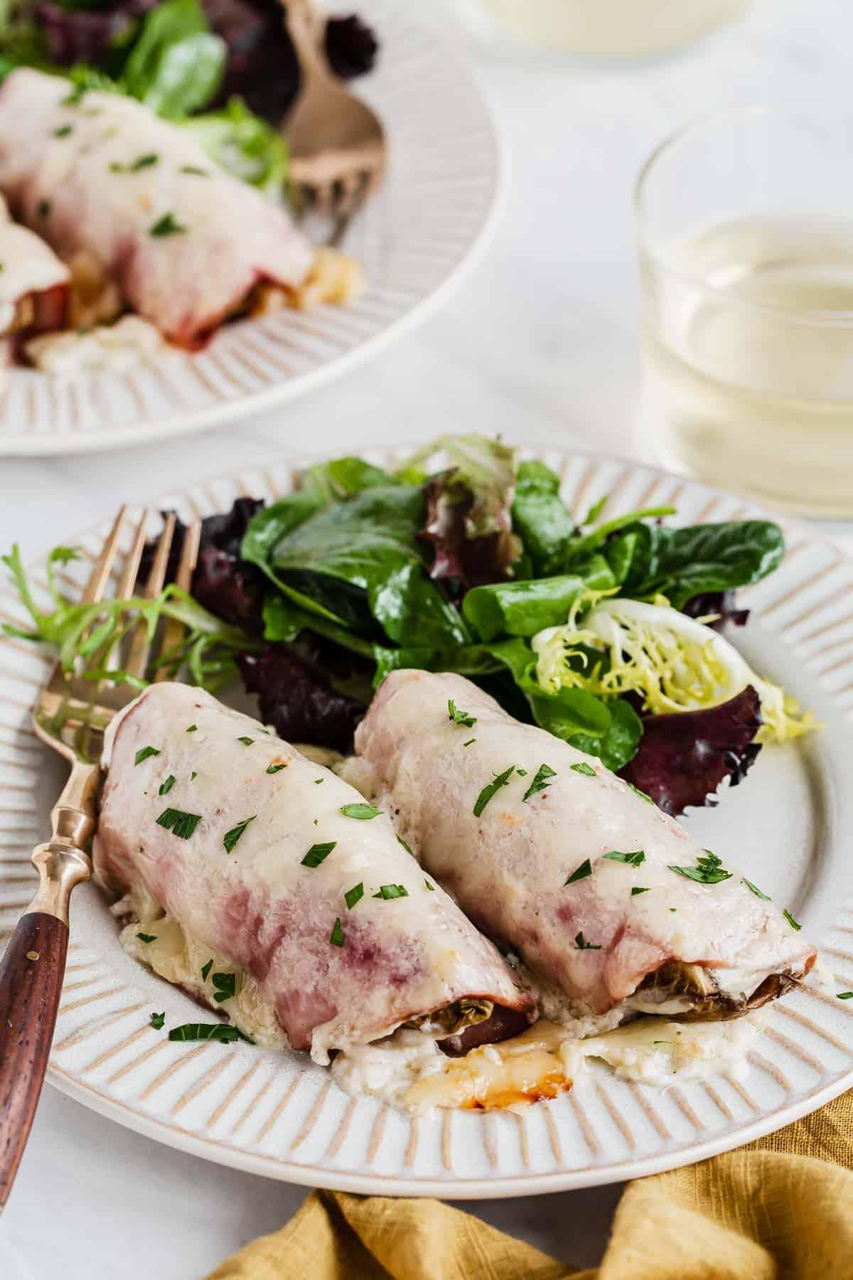 Plate of endives au gratin with side salad and fork.