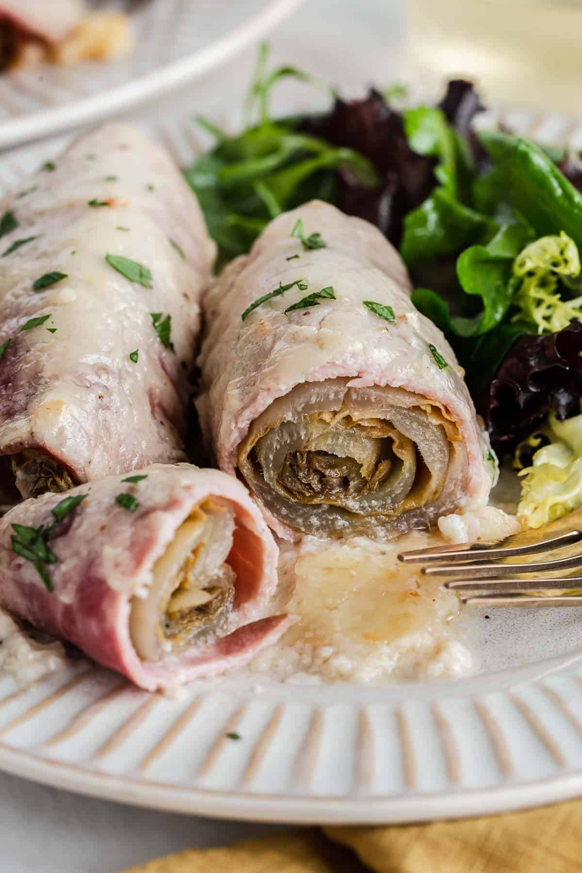 Endive wrapped in ham that has been sliced open.
