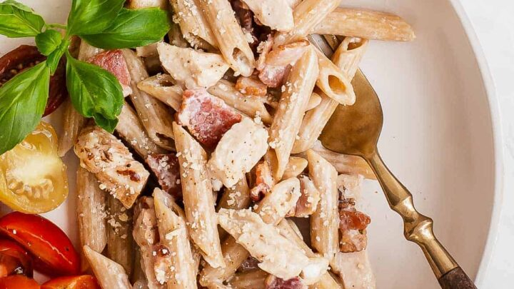 overhead shot of creamy pasta on a plate with bacon chicken and fresh tomatoes