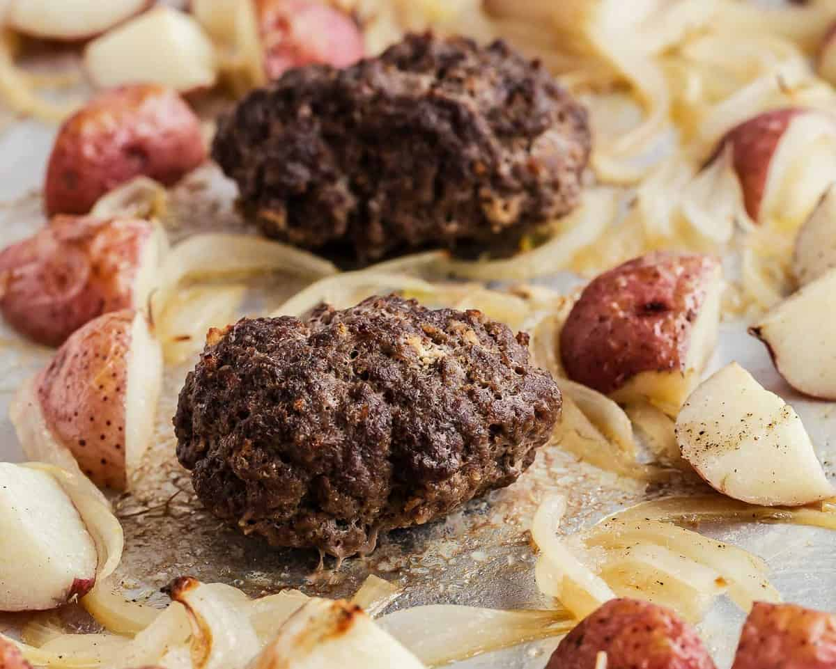 close up of beef patties surrounded by onions and potatoes