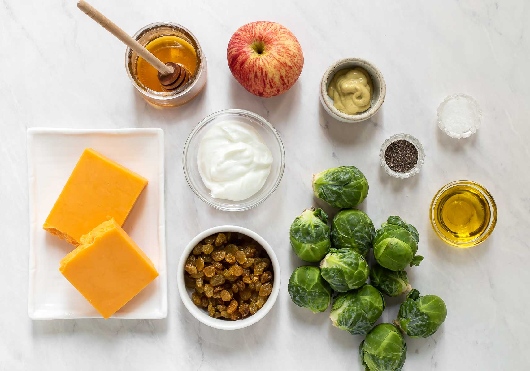 Ingredients for brussels sprout cole slaw on white table.