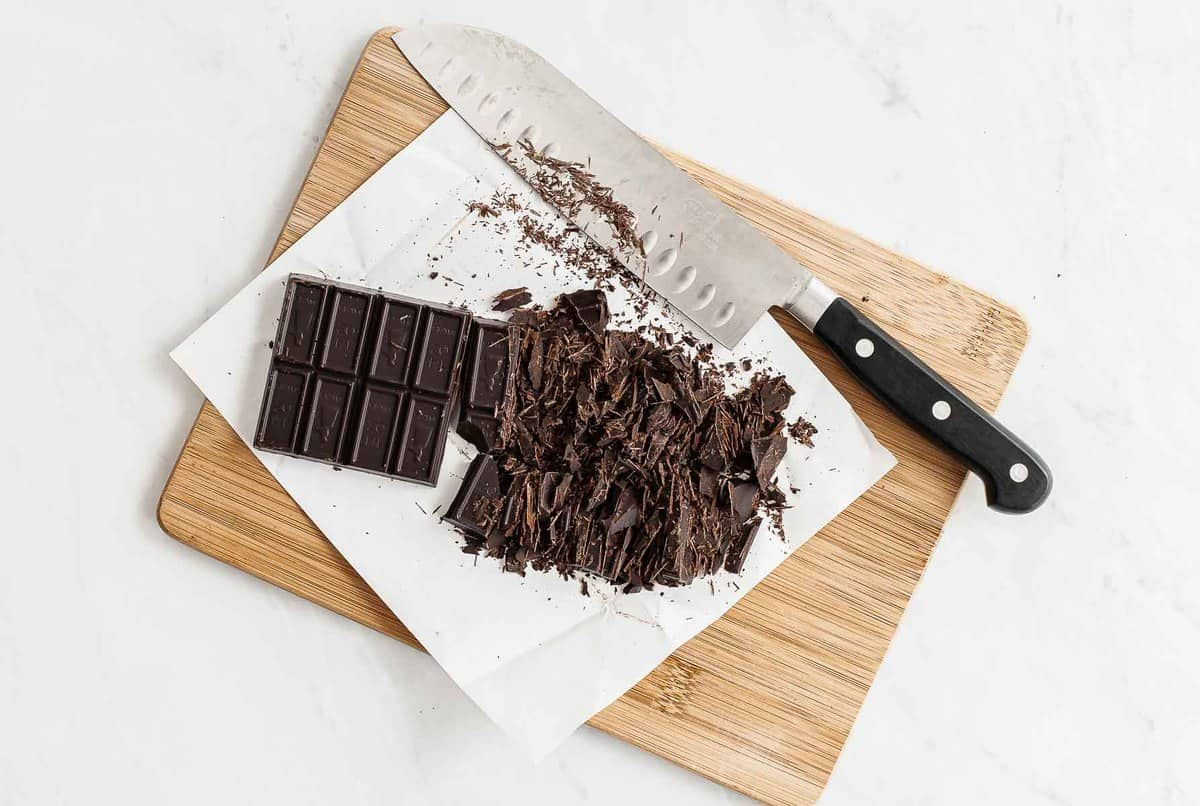 Bar of chocolate chopped on parchment paper and cutting board.