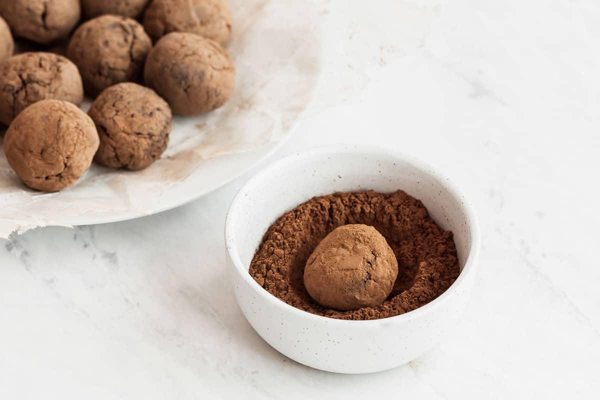 Chocolate truffle in small bowl of cocoa powder.