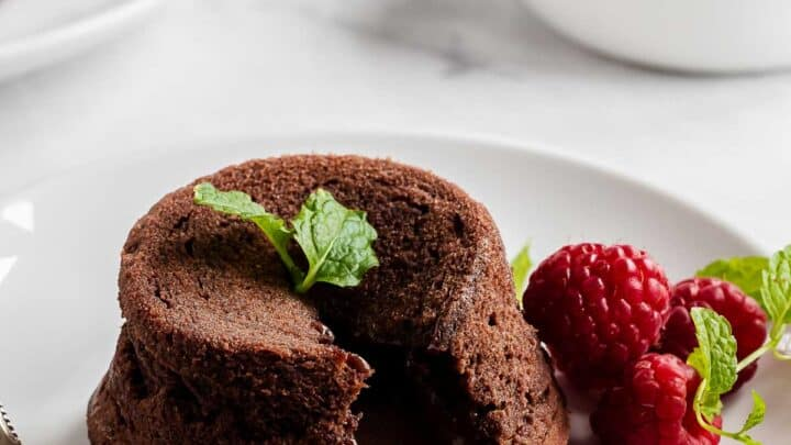 Molten chocolate cake on a plate with raspberries and fresh mint.