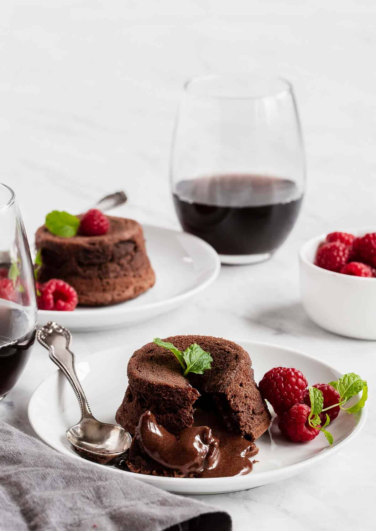 Two molten chocolate cakes on plate with berries and a glass of red wine.