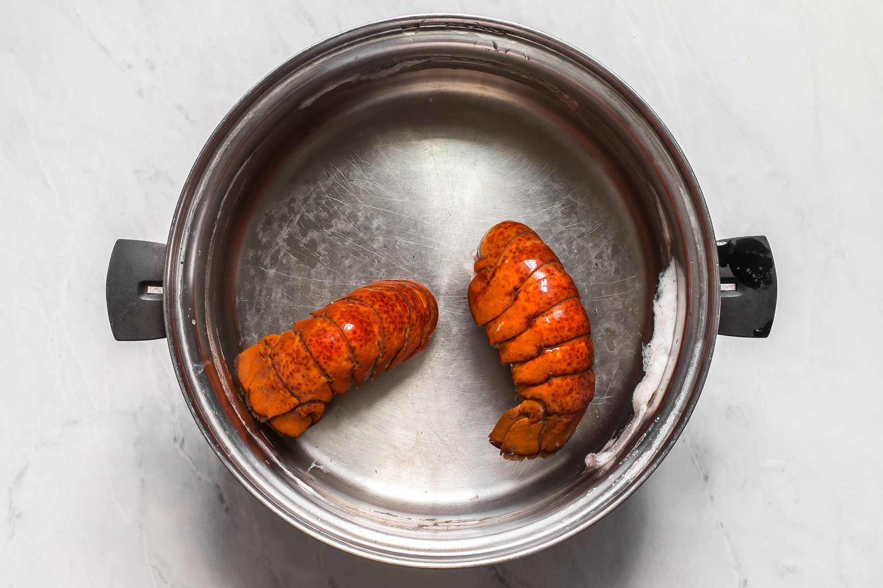 Cooked lobster tails in water pan.