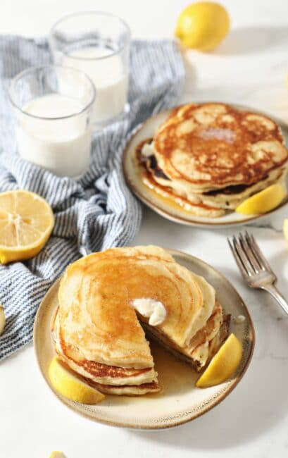 Two plates of lemon pancakes with butter and syrup on top.