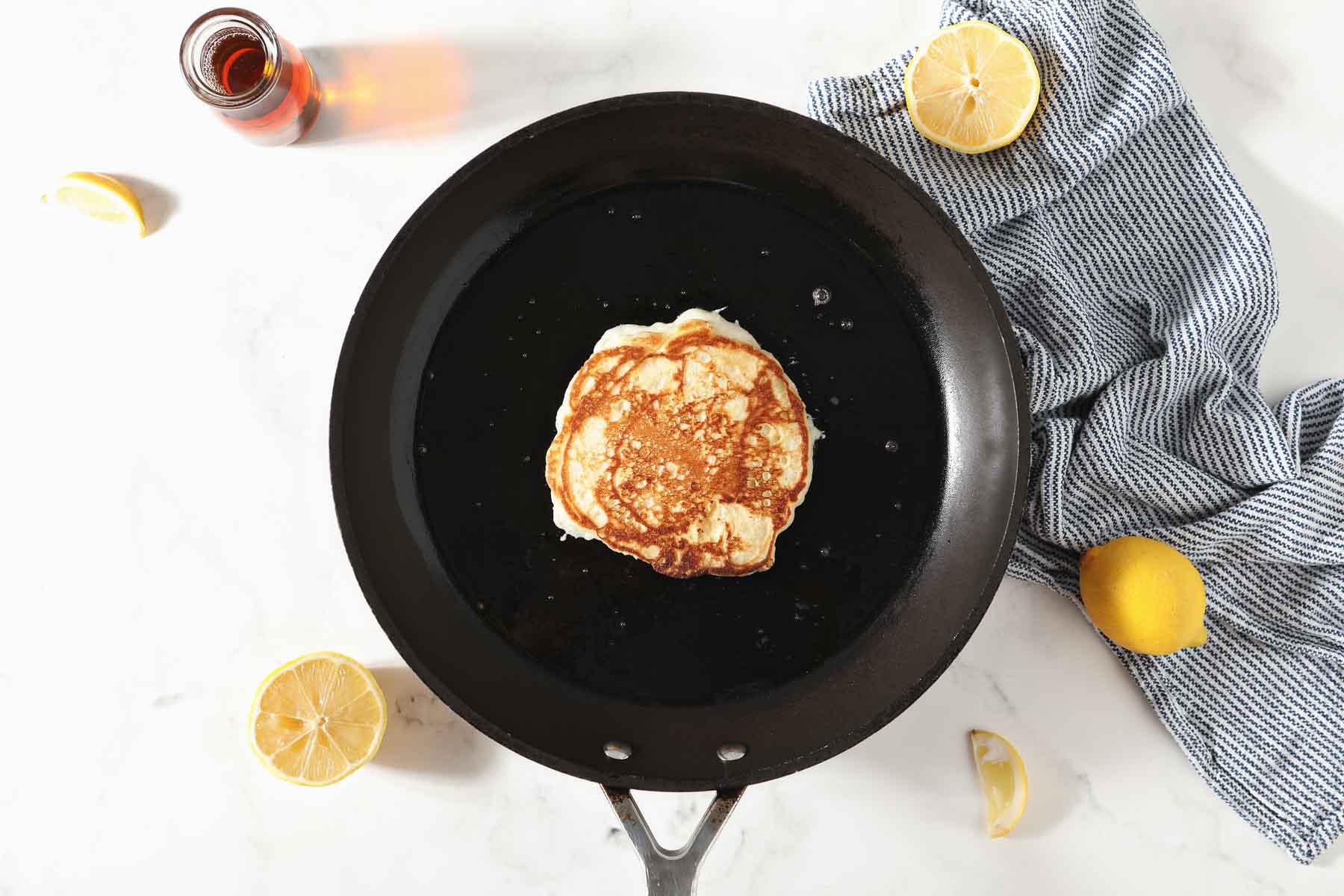 Golden brown pancakes in nonstick skillet.
