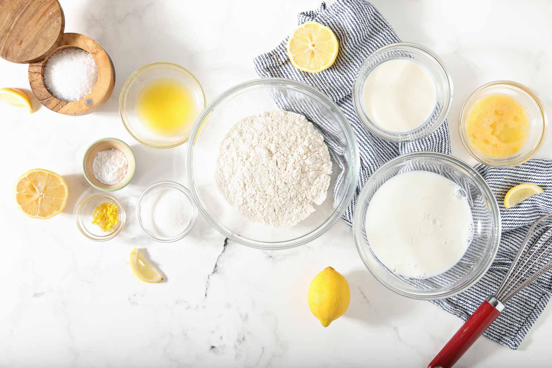 Ingredients to make lemon pancakes on white table.