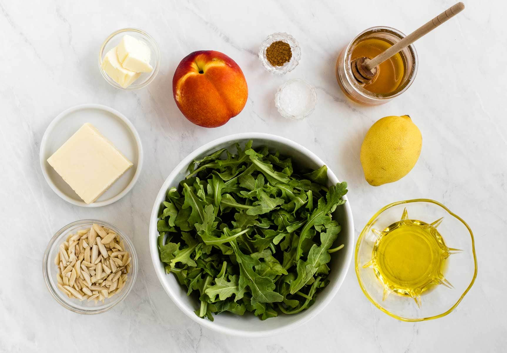 Ingredients for arugula and nectarine salad on a white table.
