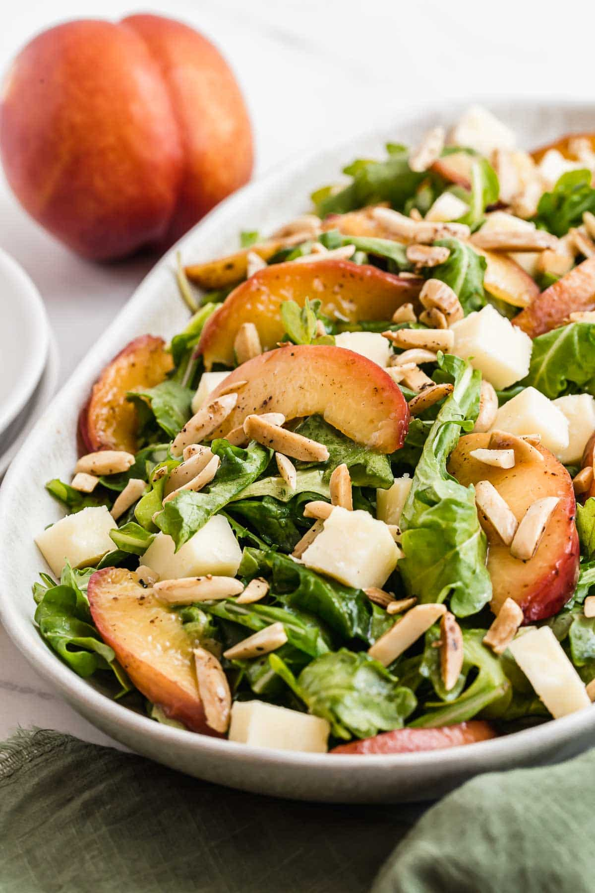 Arugula salad with sliced nectarines on top and almonds.