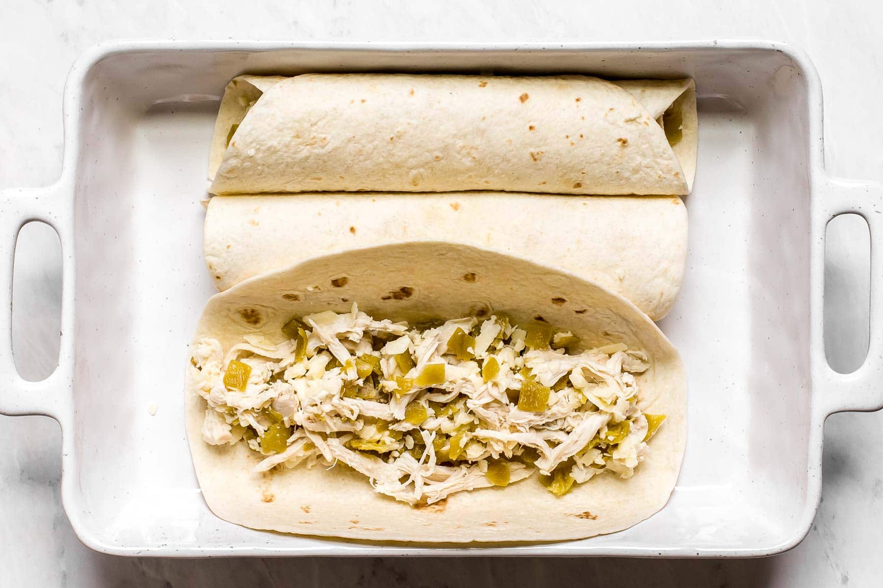 Rolling up a chicken tortilla with cheese.
