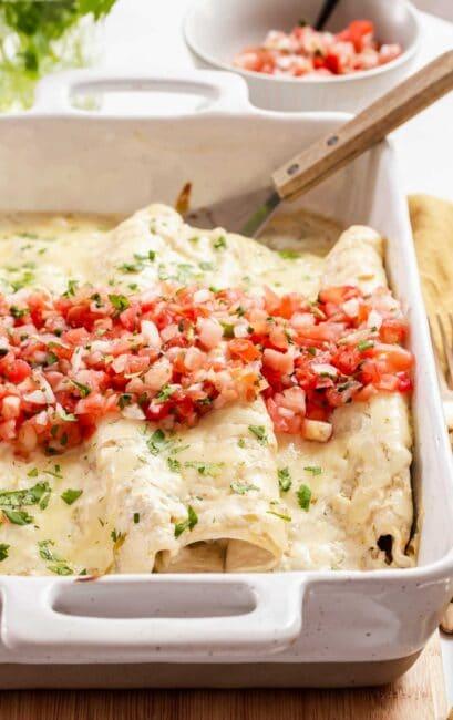 Pan of white chicken enchiladas with pico de gallo on top.
