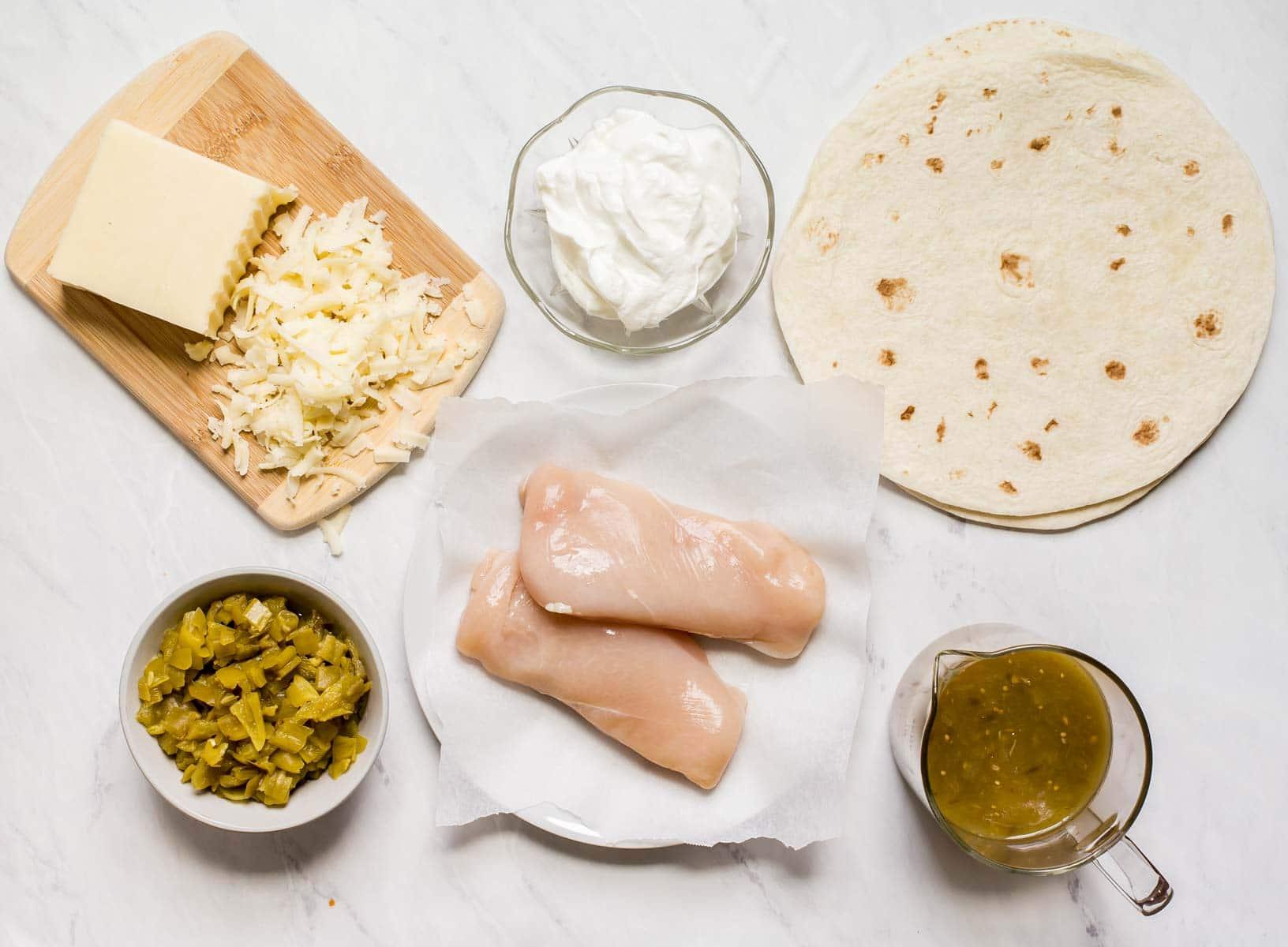 Ingredients for white chicken enchiladas on white table.