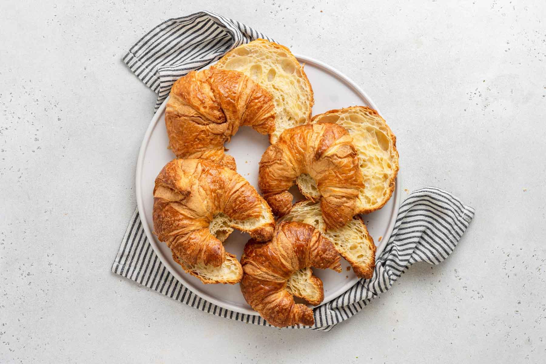 Croissants slice in half on plate.