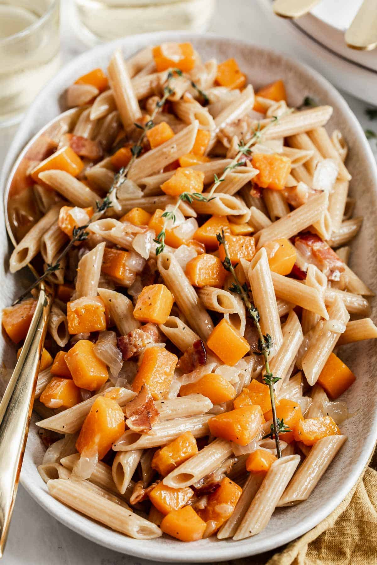 Serving tray of penne pasta with butternut squash and bacon.