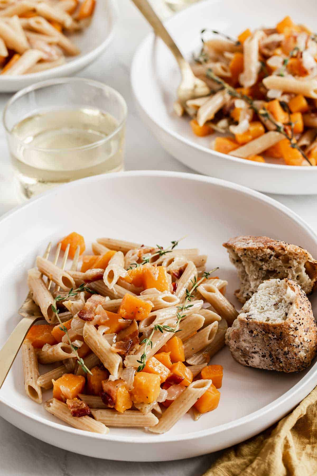 Two bowl of pasta with butternut squash cubes and bread on the side.