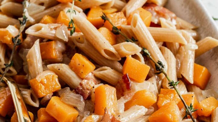 Large serving tray of penne pasta and butternut squash and thyme sprigs.