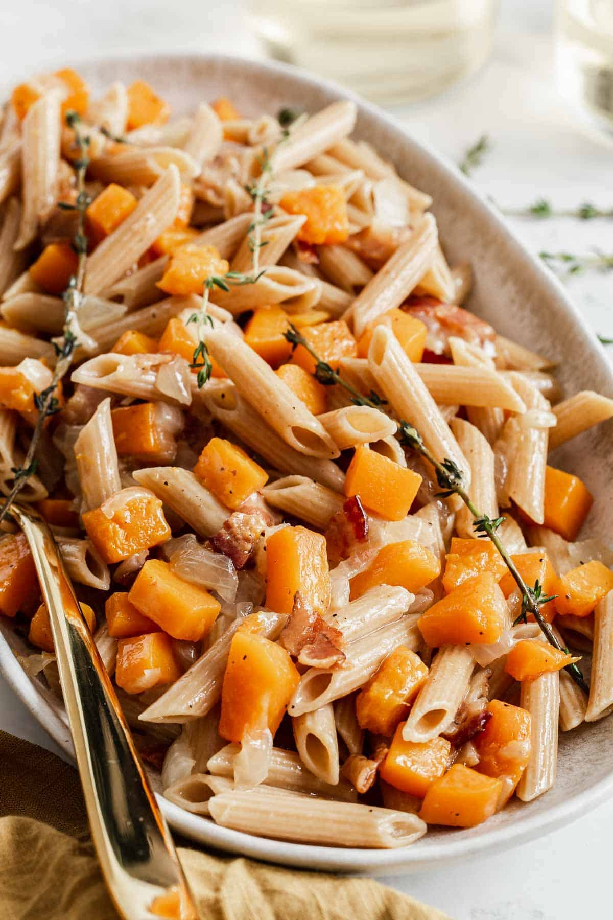 Butternut squash penne pasta on a serving plate with fresh thyme.