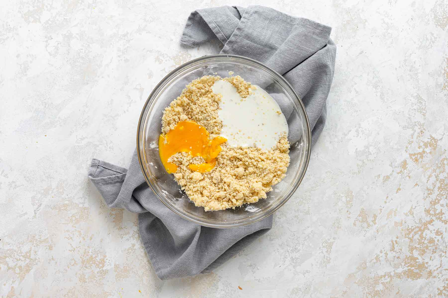 Egg yolk and cream on top of dough in bowl.