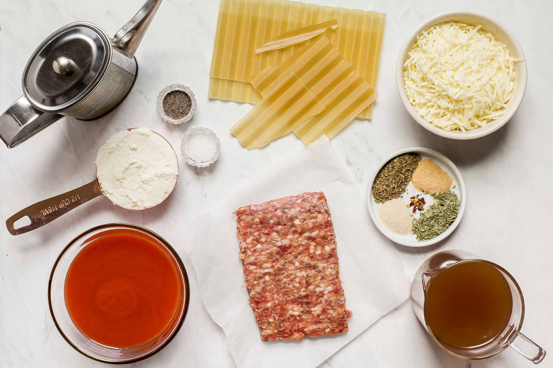 Ingredients for skillet lasagna on white table.