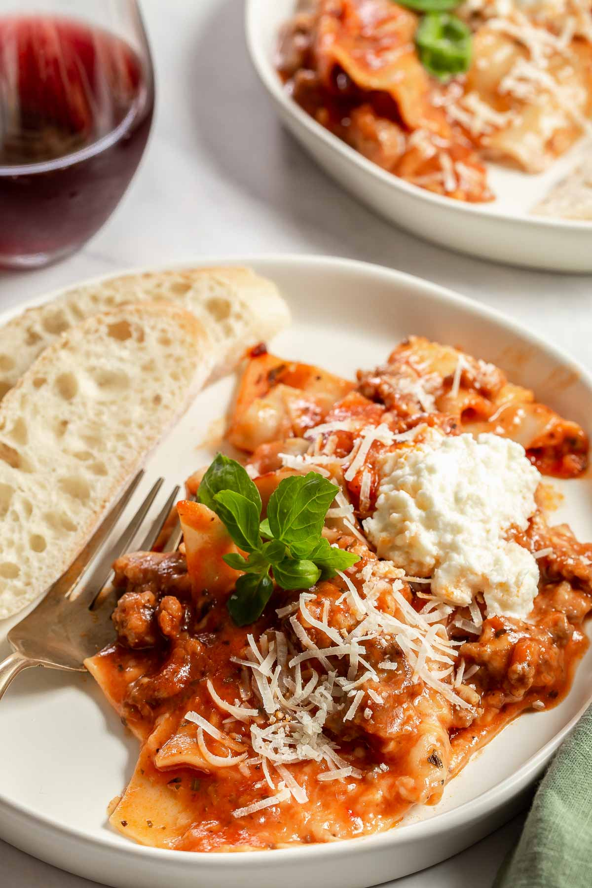 Serving of lasagna on white plate with bread.