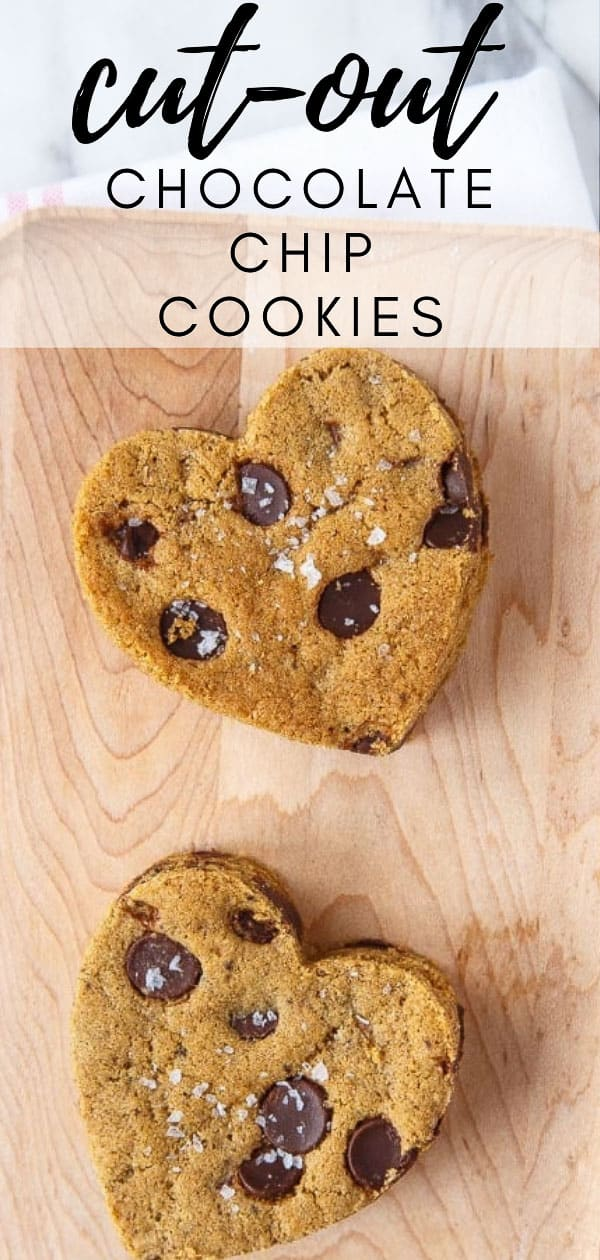 Two cut out chocolate chip cookies on a wooden plate.