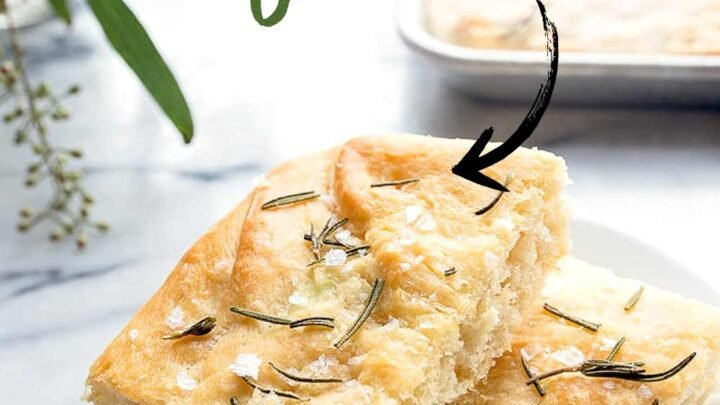 two pieces of focaccia bread with rosemary and salt on a plate
