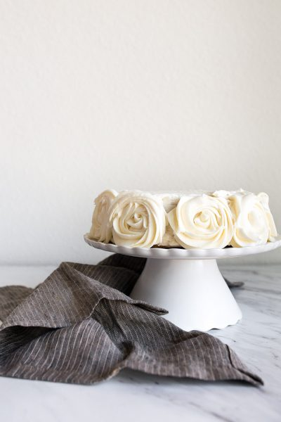 "Mini Vanilla Cake for Two people in a 6"" small round cake pan. Vanilla buttercream roses on the sides."