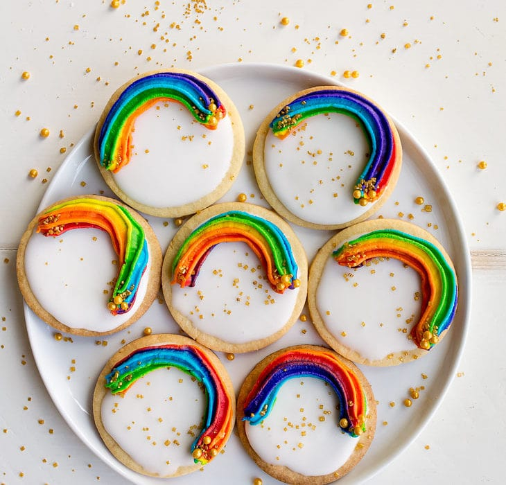 Rainbow Cookies with rainbow swirl buttercream frosting and a white Royal Icing base