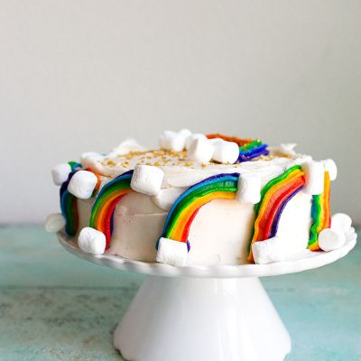 Rainbow Cake Recipe: mini rainbow cake with rainbow buttercream, marshmallow clouds and gold sprinkles. Perfect first birthday cake or rainbow baby smash cake.