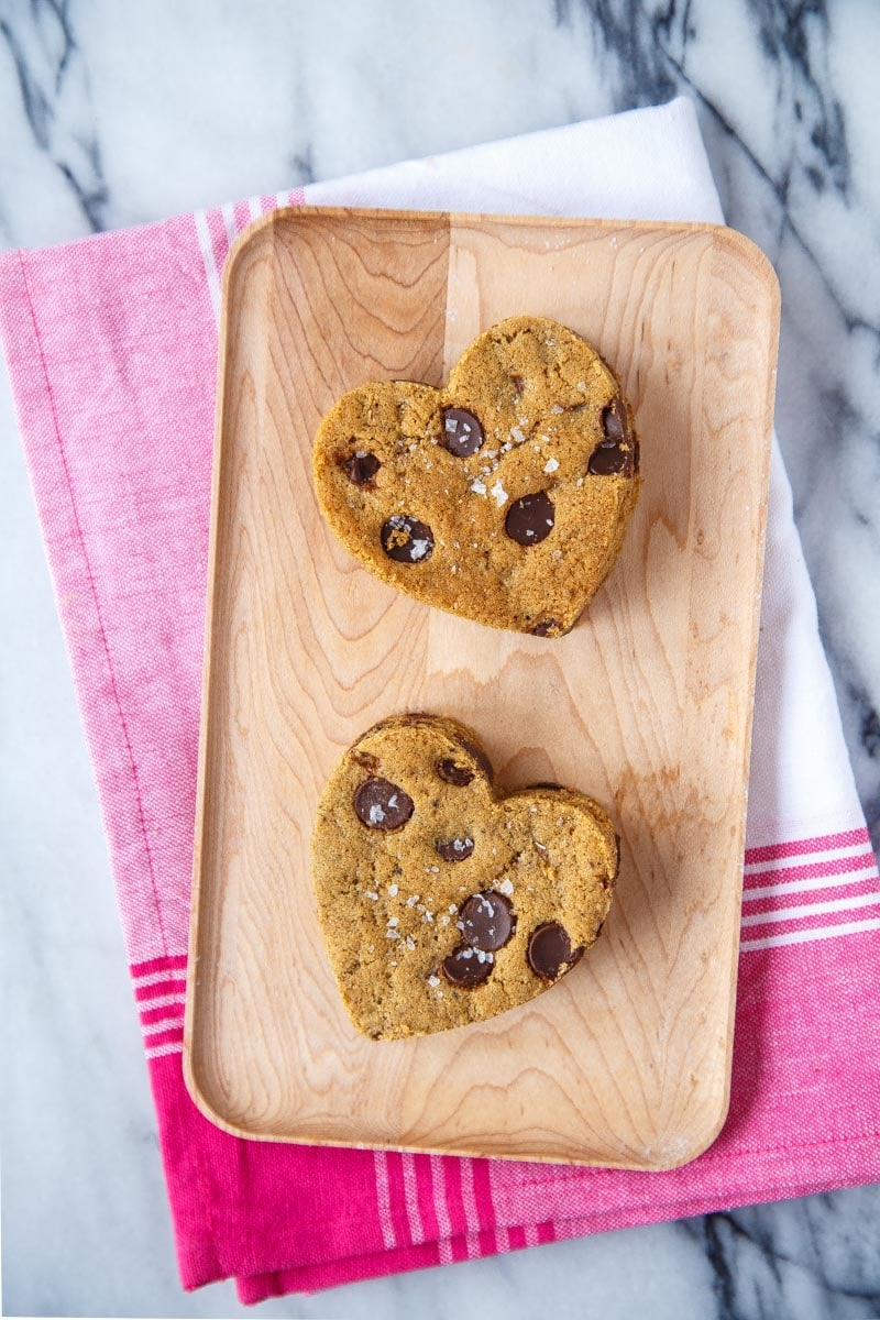 Two heart shaped cut out chocolate chip cookies on a wooden tray.