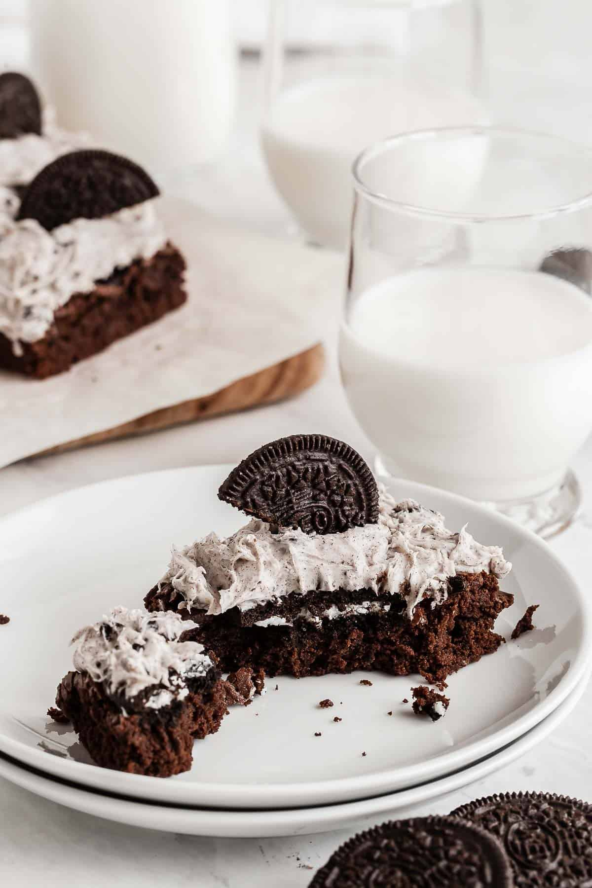 Frosted oreo brownie on white plate with bite missing.