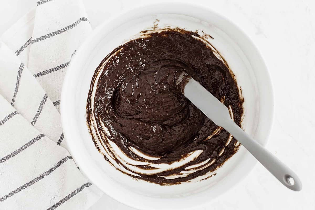 Raw brownie batter in a white bowl with grey spatula.