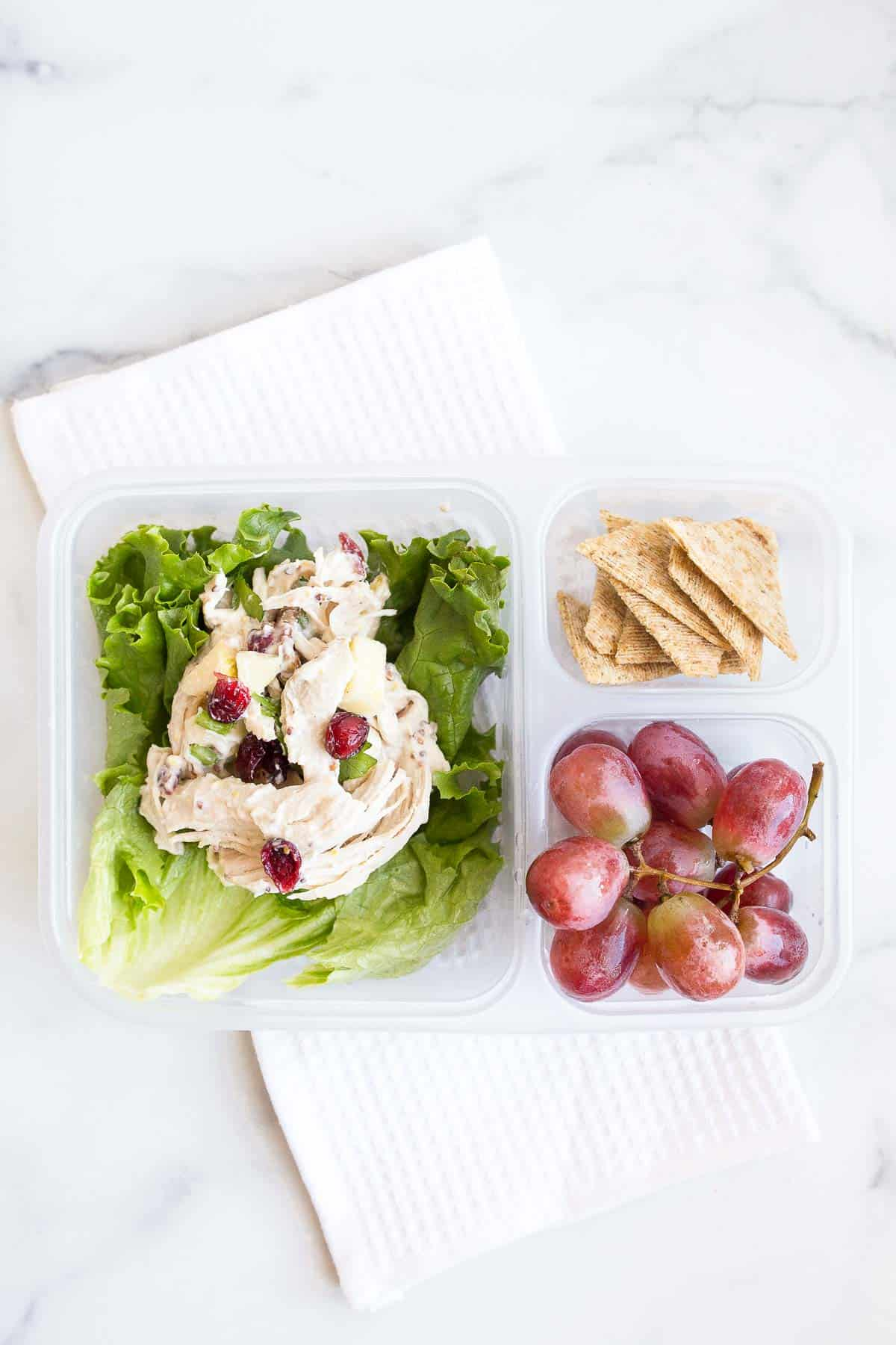 chicken salad in lunch box with crackers and grapes