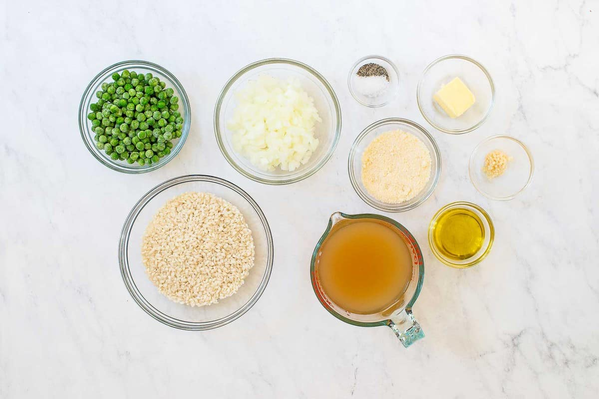 Ingredients for risotto: peas, rice, broth, spices, and vegetables.
