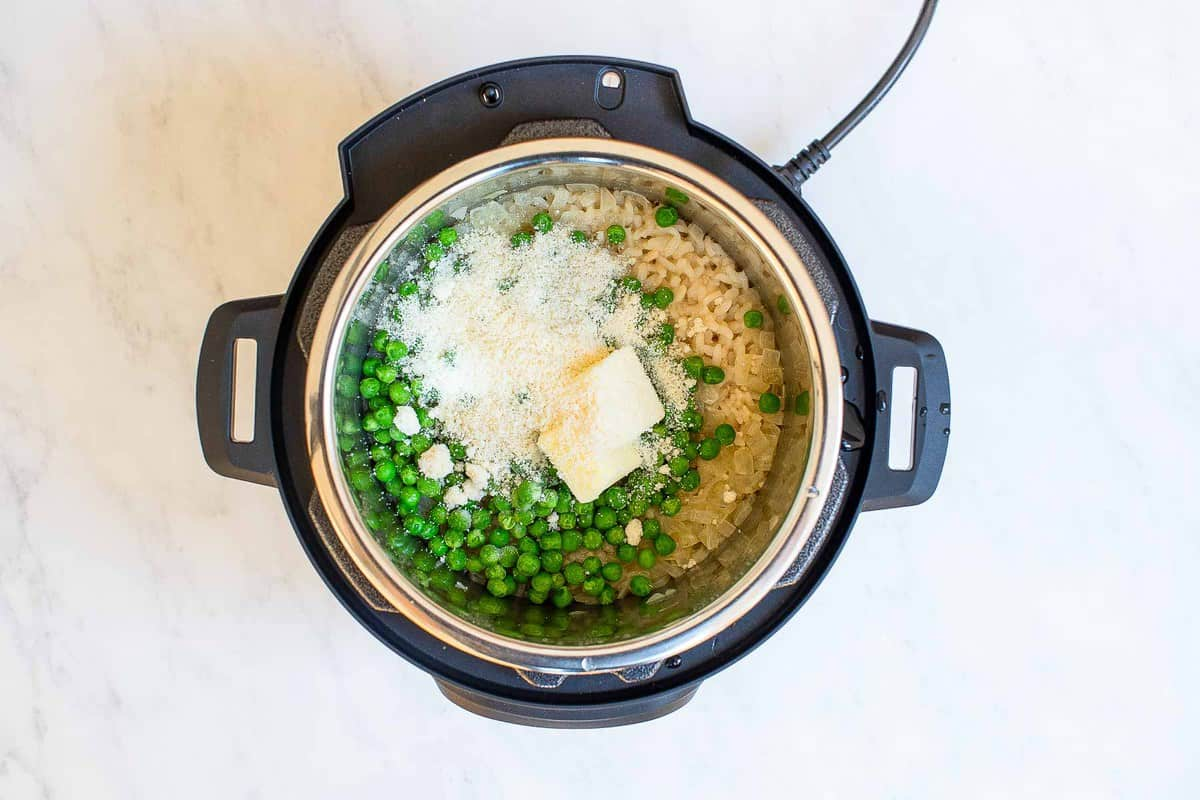 Instant pot with rice and peas and Parmesan cheese on top.
