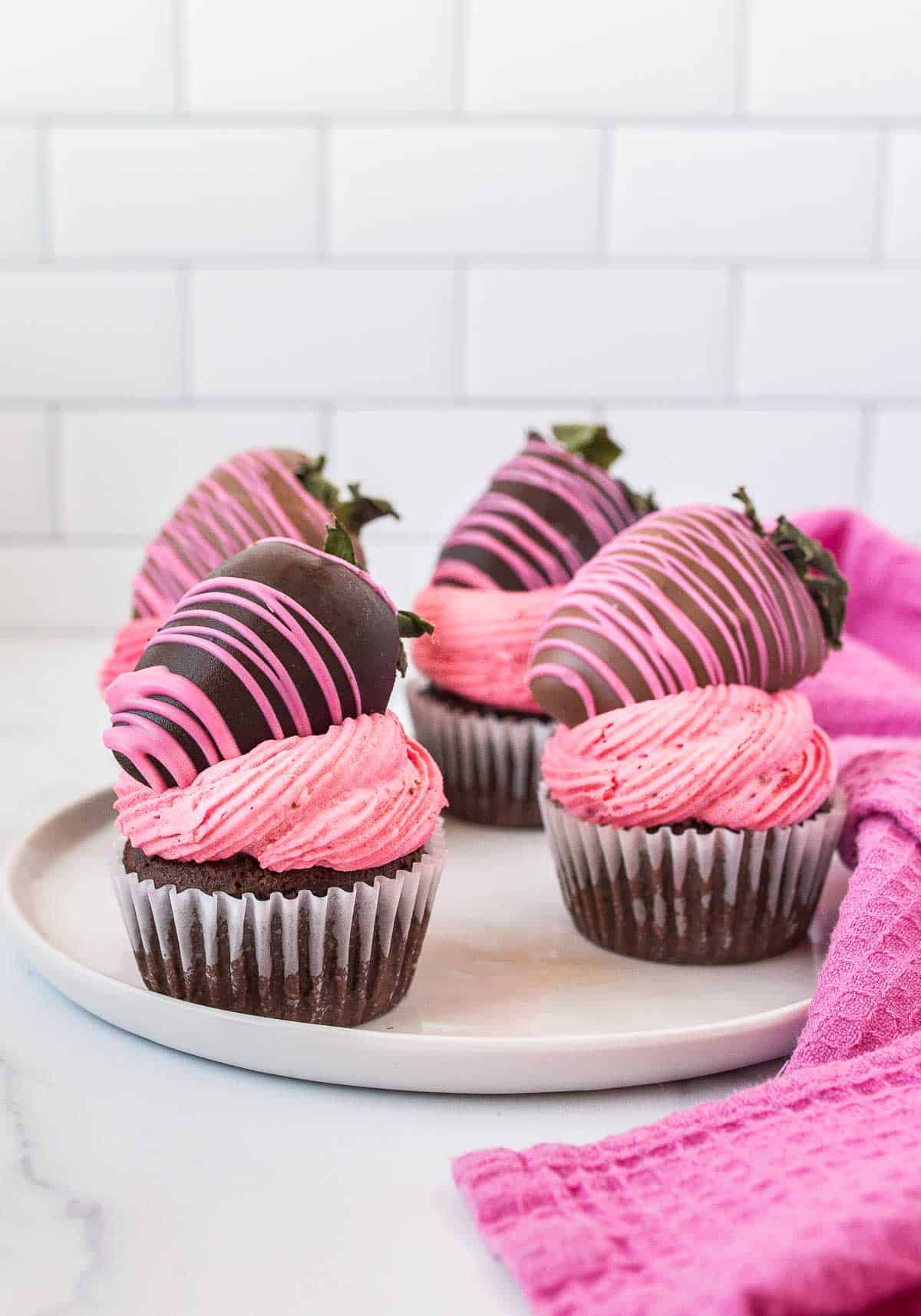 plate of chocolate cupcakes with pink frosting and chocolate covered strawberries on top.