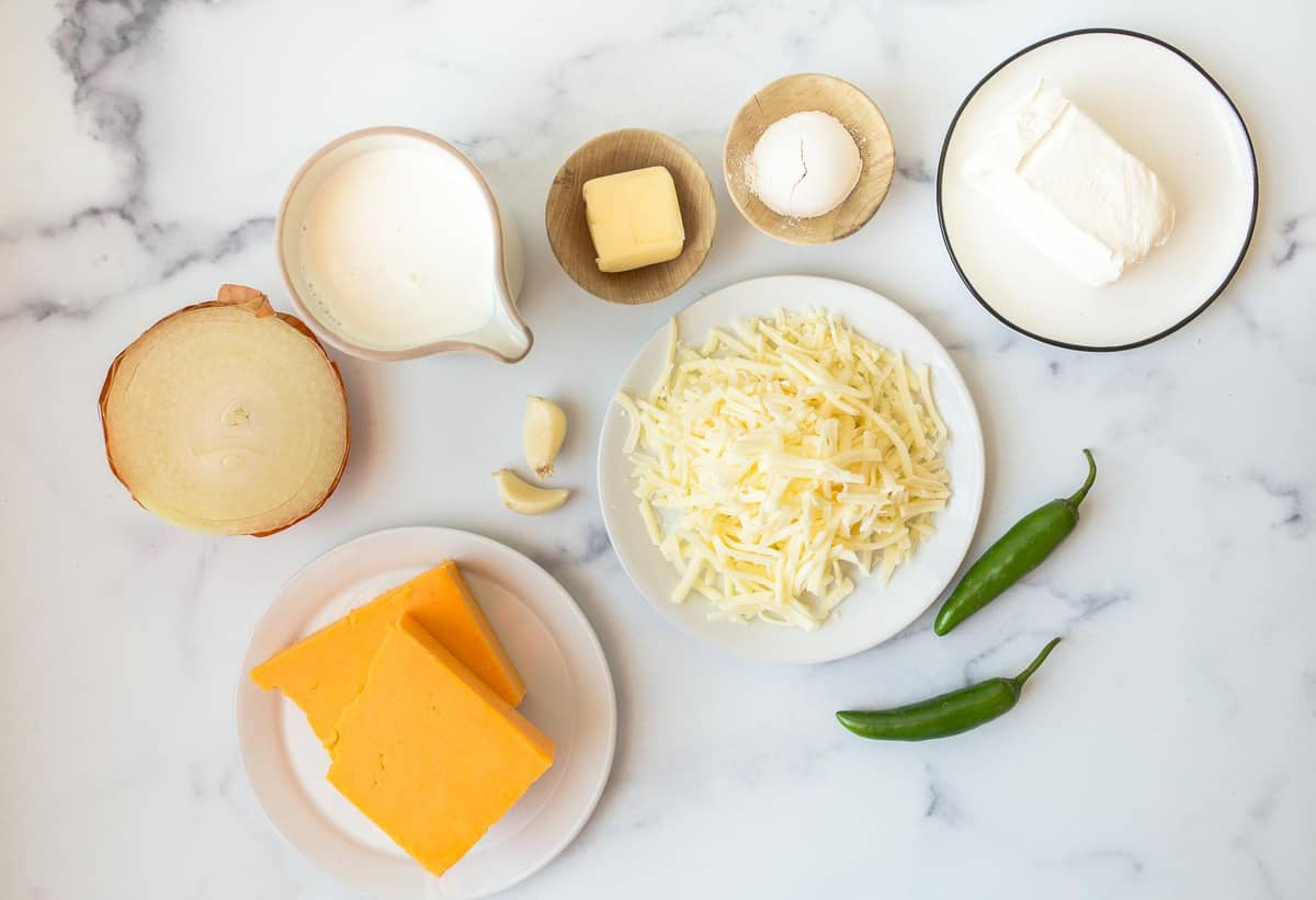 Ingredients for queso on a table: cheese, onion, cream, butter, and serranos.
