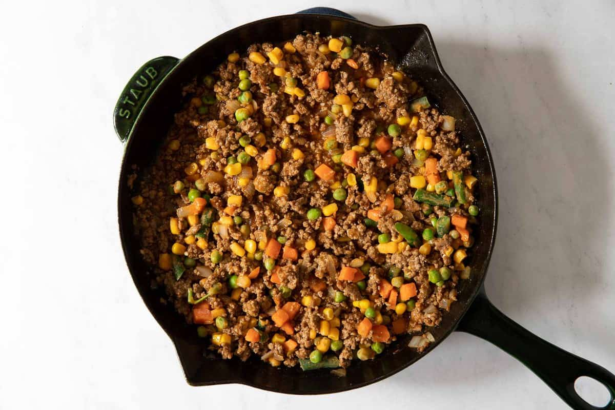 Cast iron skillet shepherds pie with ground beef and mixed vegetables.