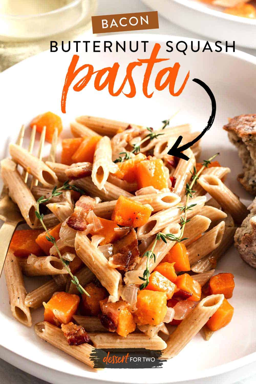 White plate with bacon butternut squash and penne pasta.